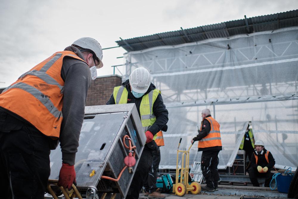 men load equipment on site